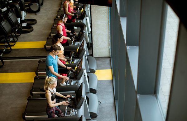Top view at group of young people running on treadmills in modern gym