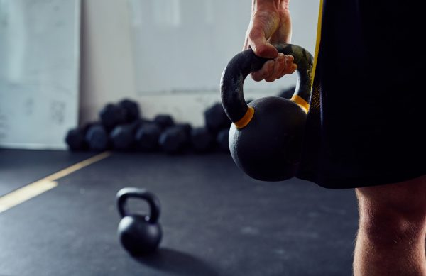 Closeup of kettlebell held by athlete at the gym
